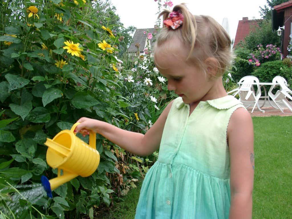 Kind mit Gießkanne im Kleingarten
