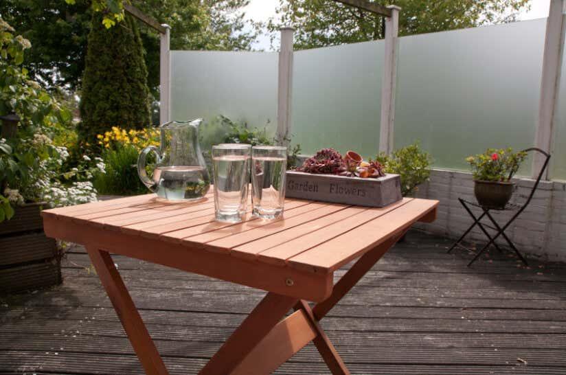 Terrassentisch im Garten mit drei Wassergläsern