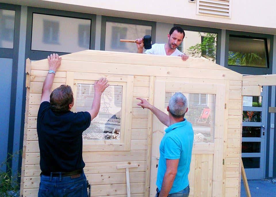 Mit vereinten Kräften: Das Gartenhaus wird aufgebaut.