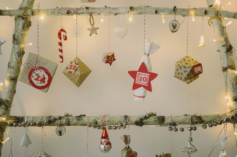 Kleine Christbaumanhängerchen und Geschenke schmücken die Äste.