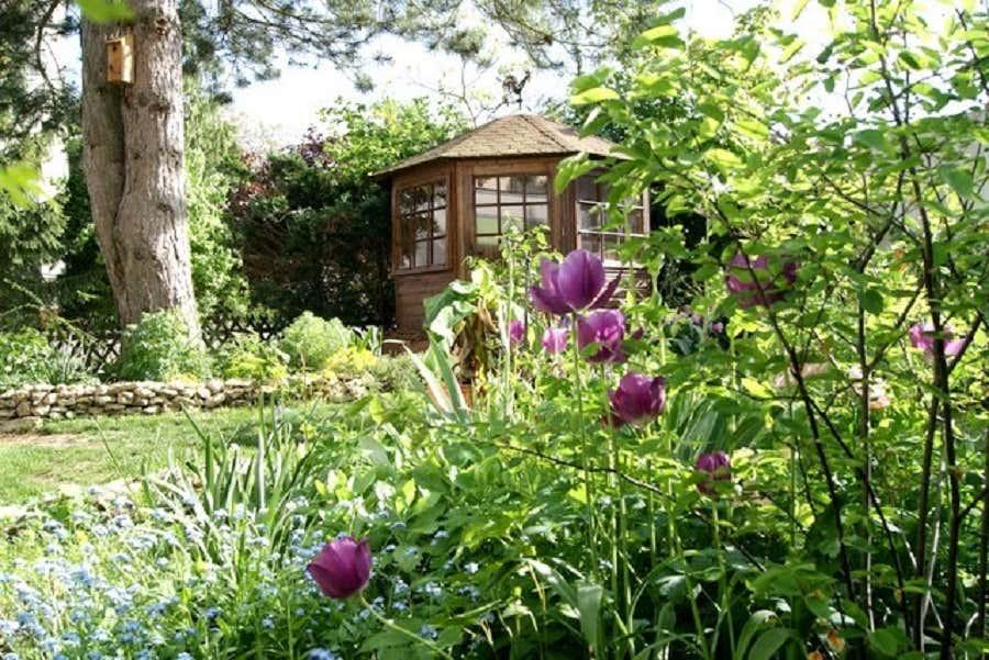 Das rustikale kleine Gartenhaus vollendet das malerische Ambiente des Gartens.