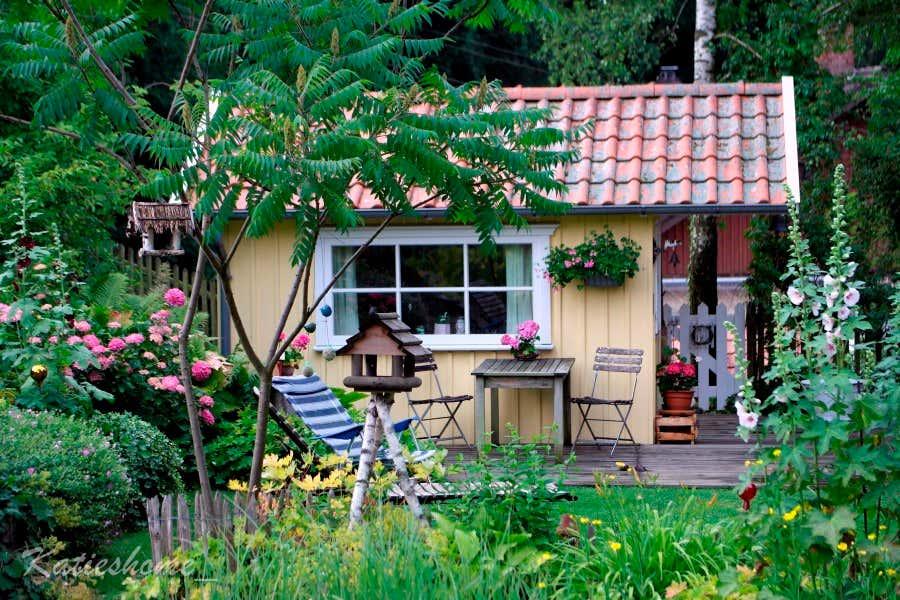 Die gelbe Schwedenhütte am Gartenteich.