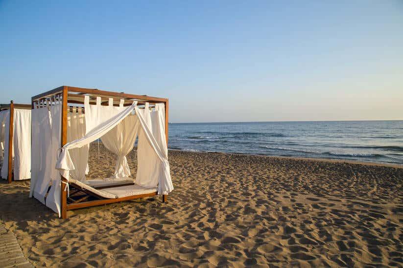 Holzpavillon mit weißen Vorhängen am Strand
