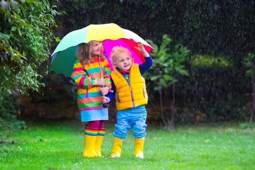 Kinder stehen unter Regenschirm